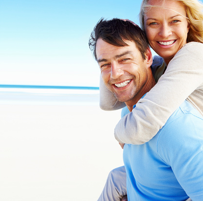 A Man Giving A Woman A Piggyback Ride On The Beach Stock Photo - Download Image Now