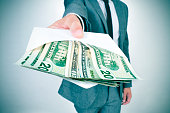 istock man giving an envelope full of american dollar bills 1130901144