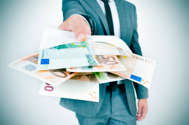 man giving an envelope full of euro bills stock photo