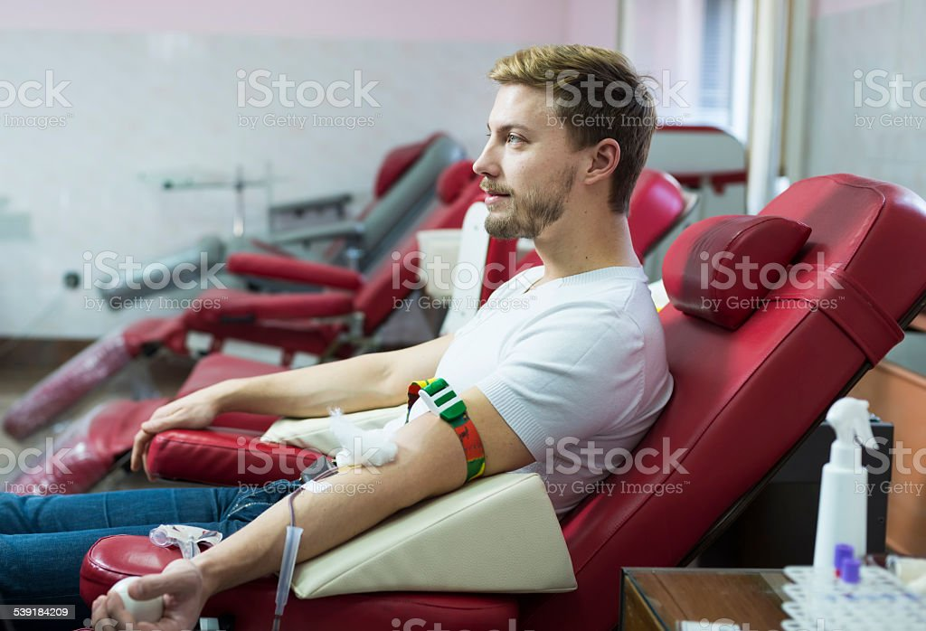 Man giving blood donation stock photo