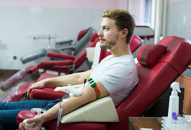 man giving blood donation - blood donation stock pictures, royalty-free photos & images