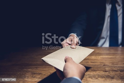 istock A man giving bribe money in a brown envelope to another businessman in the dark 876037340