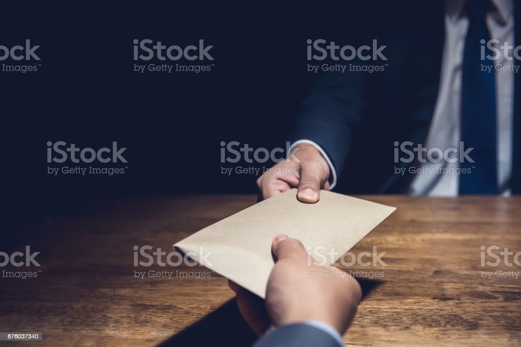A man giving bribe money in a brown envelope to another businessman in the dark stock photo