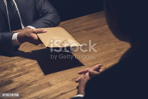 istock A man giving bribe money in a brown envelope to another businessman 876018768