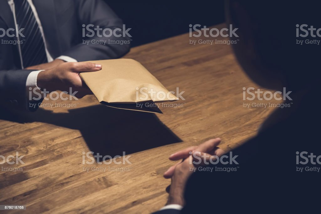 A man giving bribe money in a brown envelope to another businessman stock photo