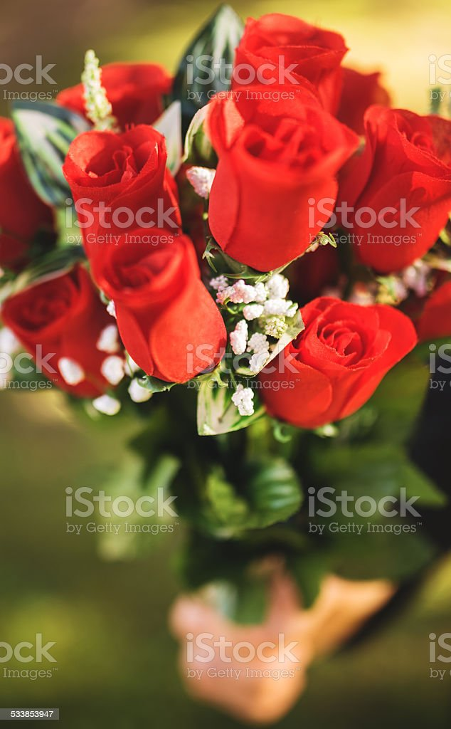 man hiding bunch of rose