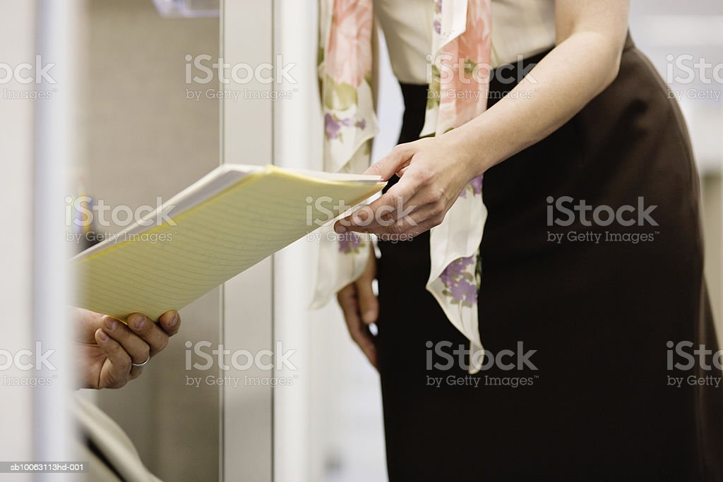 Man giving document to woman in office, mid section photo libre de droits