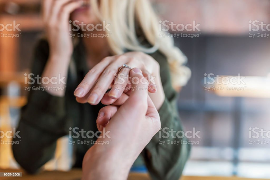 Photo of Unrecognizable Husband gifting a diamond ring to Caucasian...
