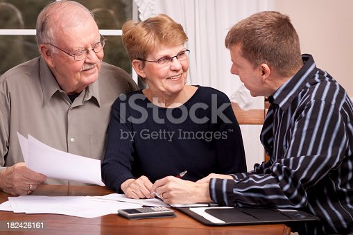 istock Man giving financial advisor to senior couple smiling 182426161