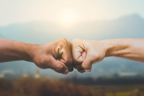 Man giving fist bump in sun rising nature background. power of teamwork concept. vintage tone Man giving fist bump in sun rising nature background. power of teamwork concept. vintage tone dedication stock pictures, royalty-free photos & images