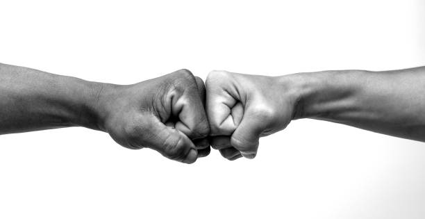 Man giving fist bump, monochrome, black and white image. Man giving fist bump, monochrome, black and white image. dedication stock pictures, royalty-free photos & images