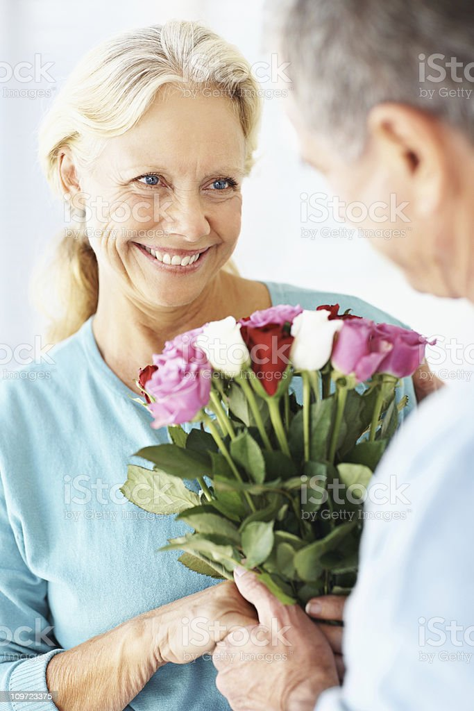 Man giving flowers to a woman on their anniversary royalty-free stock photo