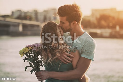 Young man giving flowers to his girlfriend outdoor.Image is intentionally toned.