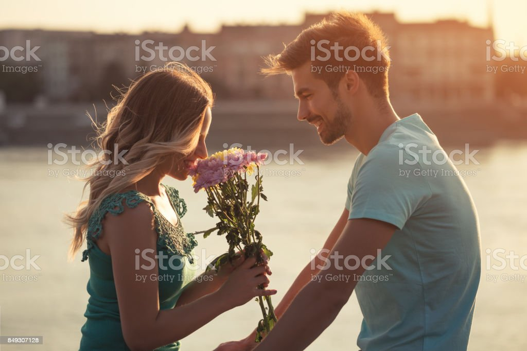 Man giving flowers to his girlfriend stock photo