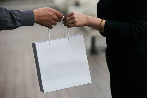 男子送禮物在紙袋給婦女, 特寫圖像檔