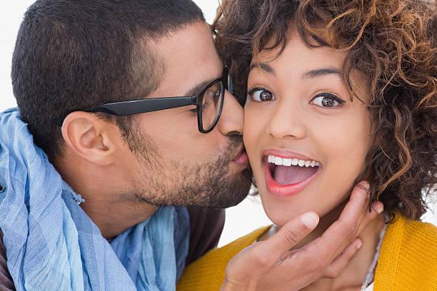 man giving girlfriend kiss on the cheek - brunette woman eyeglasses kiss man foto e immagini stock