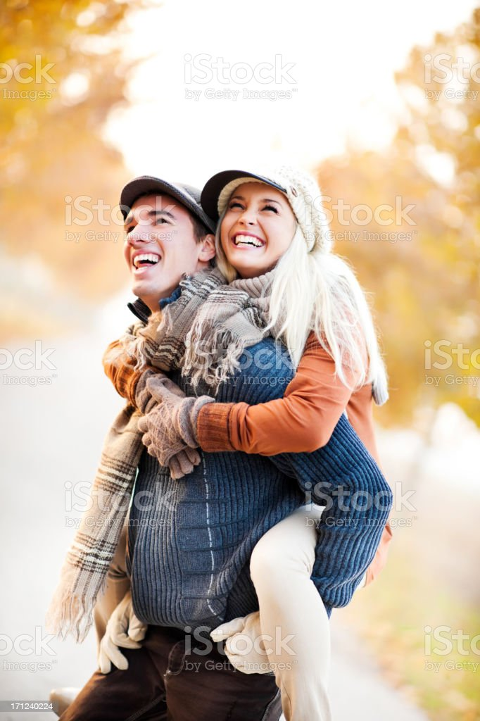 Man giving his girlfriend a piggyback ride royalty-free stock photo