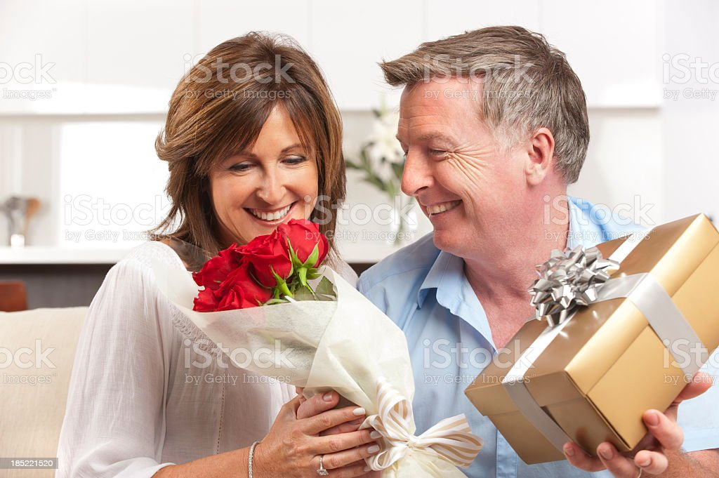 Man giving his happy wife a gift and roses stock photo