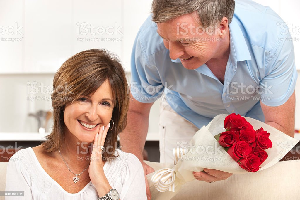 Man giving his happy wife roses stock photo
