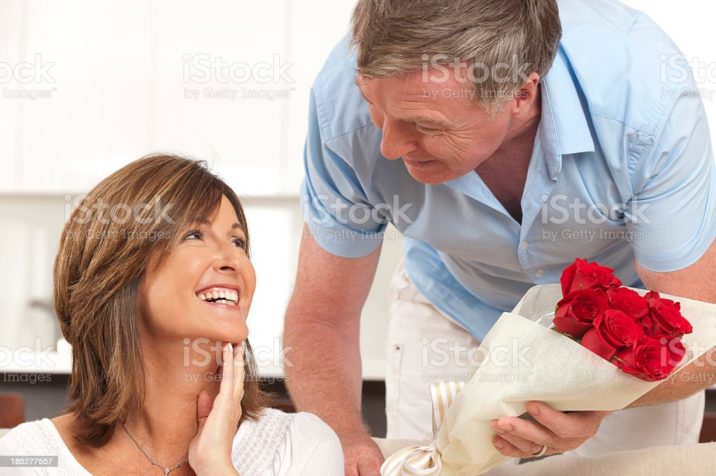 Man giving his happy wife roses royalty-free stock photo