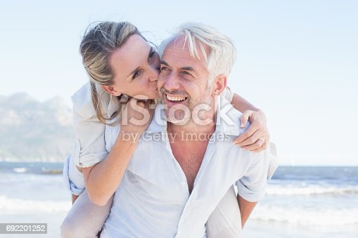istock Man giving his smiling wife a piggy back at the beach 692201252