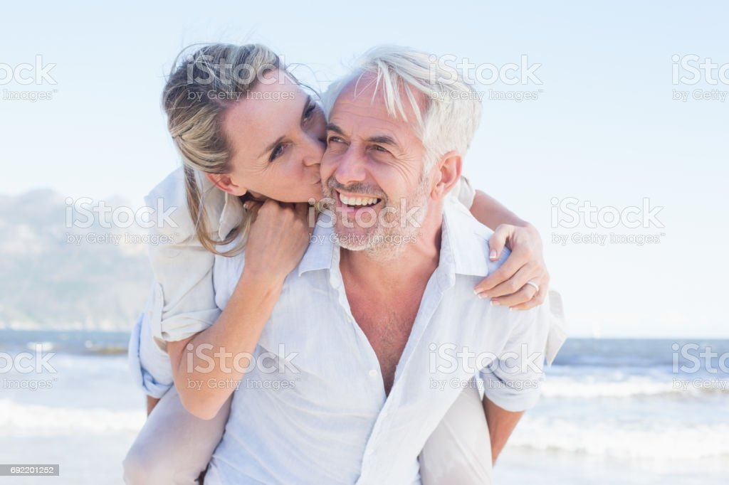Man giving his smiling wife a piggy back at the beach stock photo
