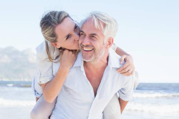 man die geeft zijn lachende vrouw een piggy rug op het strand - ouder volwassenen koppel stockfoto's en -beelden