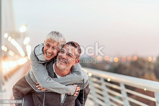 690538774 istock photo Man giving his smiling wife a piggy back 1062948358