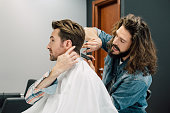 Man giving instructions to his hairdresser