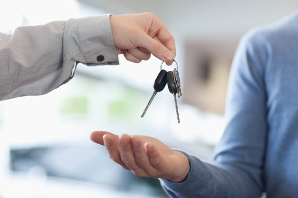 Man giving keys to someone Man giving keys to someone in a car shop car key stock pictures, royalty-free photos & images