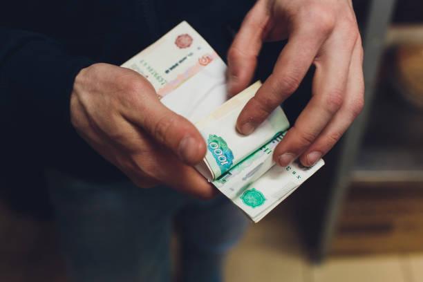 돈, 러시아 루블 지폐를 주는 사람, 어두운 사무실에서 자신의 책상을 통해-뇌물 및 부패 개념. 러시아 루블 지폐. 금융 테마. 남자의 손에 지폐 더미. - 러시아 루블 뉴스 사진 이미지