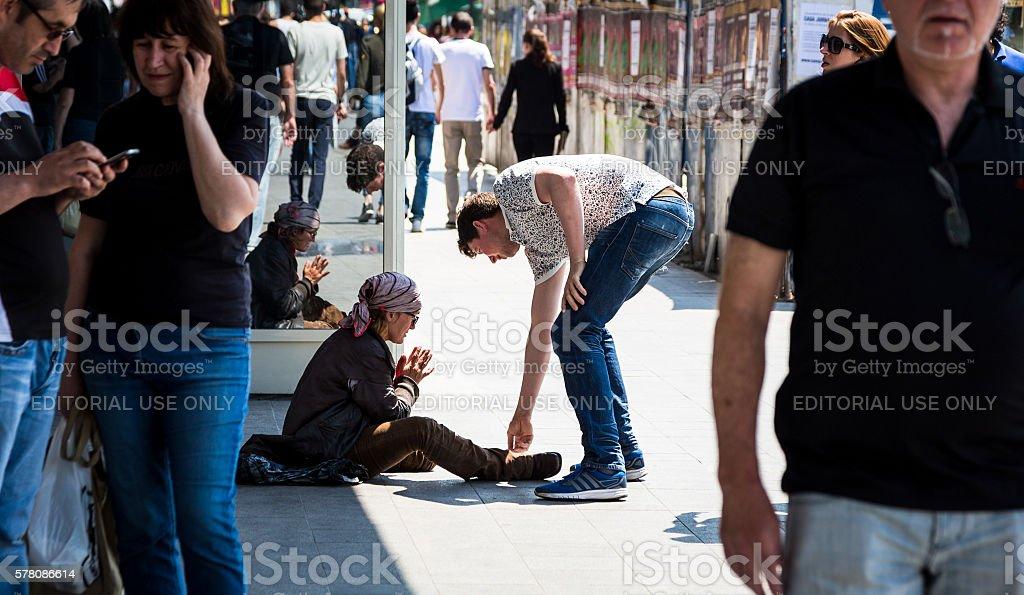 Man giving money to homeless street woman in Bucharest, Romania stock photo