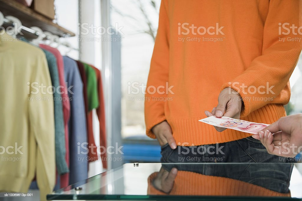 Man giving money to sales clerk in store, close-up, mid section royalty-free stock photo