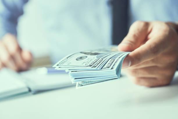 Mann, der uns Dollar-Banknoten gibt und Bargeld in Händen hält. Gelddarlehenskonzept. Tonbild. – Foto