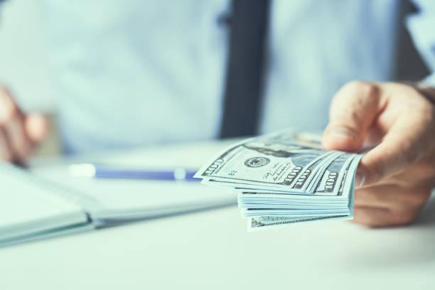 Mann gibt uns Geld-Dollar-Banknoten und hält Bargeld in der Hand. Geldkreditkonzept. Getöntes Bild. – Foto