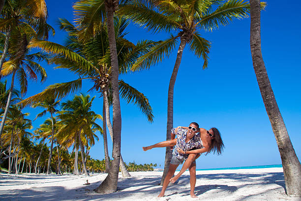 Man giving piggyback ride to girlfriend at the beach Happy young couple having beach fun piggybacking laughing together during summer holidays vacation on tropical caribbean beach. real couples making love stock pictures, royalty-free photos & images