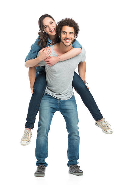 Man Giving Piggyback Ride To Her Girlfriend Portrait Of Young Man Piggybacking Her Girlfriend Isolated On White Background piggyback stock pictures, royalty-free photos & images