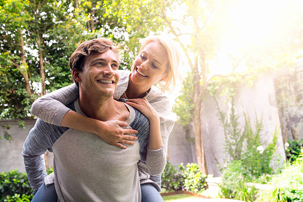 Man giving piggyback ride to woman in backyard stock photo