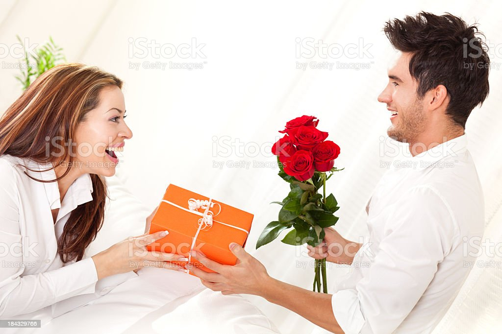 Человек, давая подарок и Букет из красных роз, женщина стоковое фото