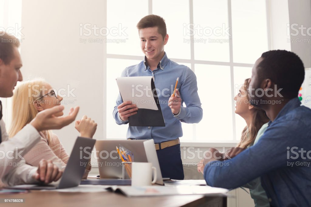 Man giving presentation to colleagues in office stock photo