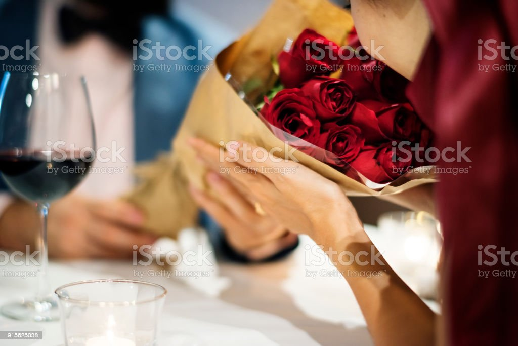 Man giving red rose bouquet stock photo