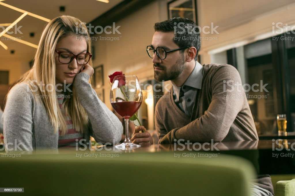 Man giving red rose to sad women in bar stock photo