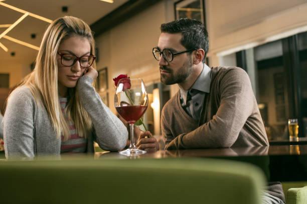 Man giving red rose to sad women in bar stock photo
