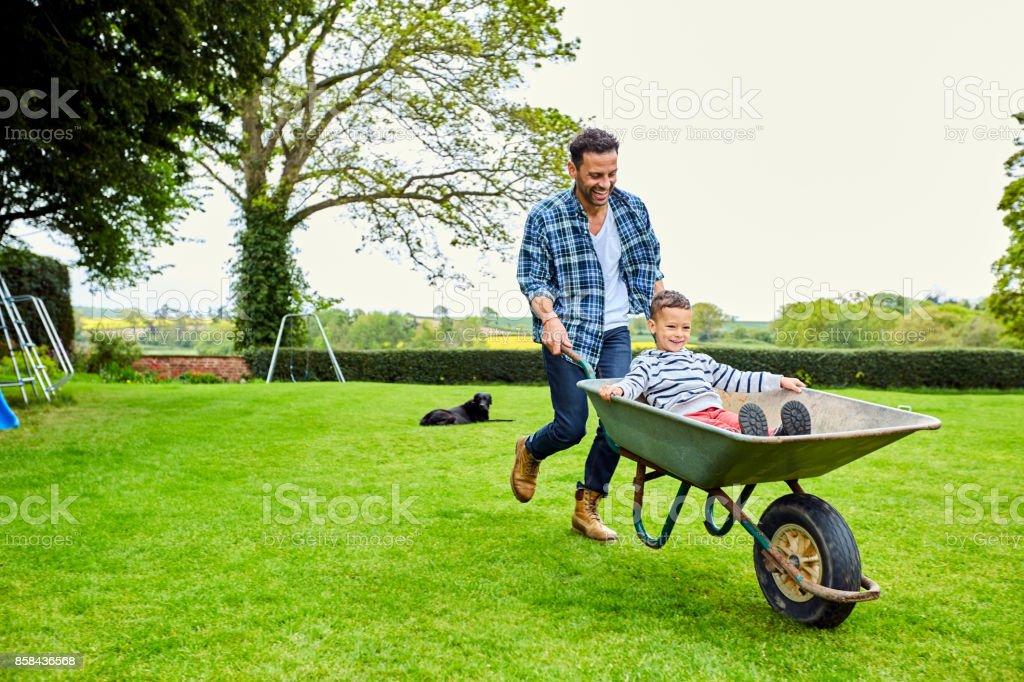 Man giving son ride in wheelbarrow stock photo