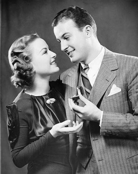 man giving to fiance engagement ring in studio, (b&w), portrait - 1940s style stock photos and pictures