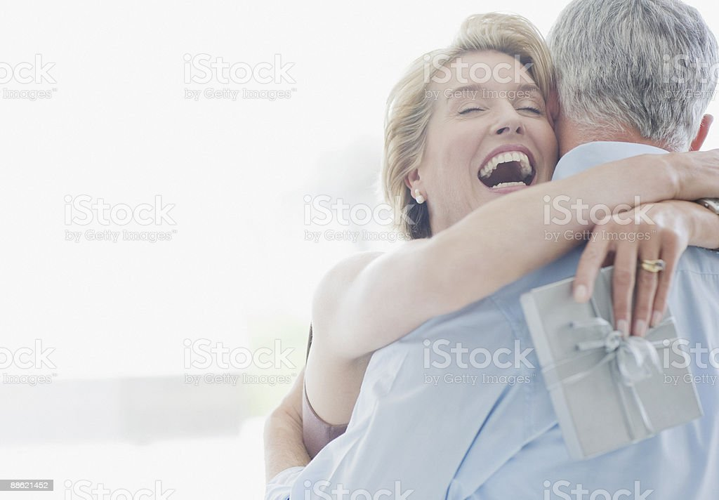 Man giving wife anniversary gift stock photo