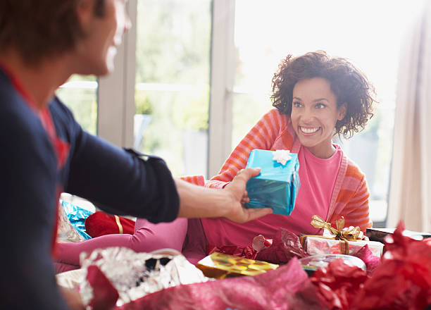 Man giving wife Christmas gift  birthday present stock pictures, royalty-free photos & images
