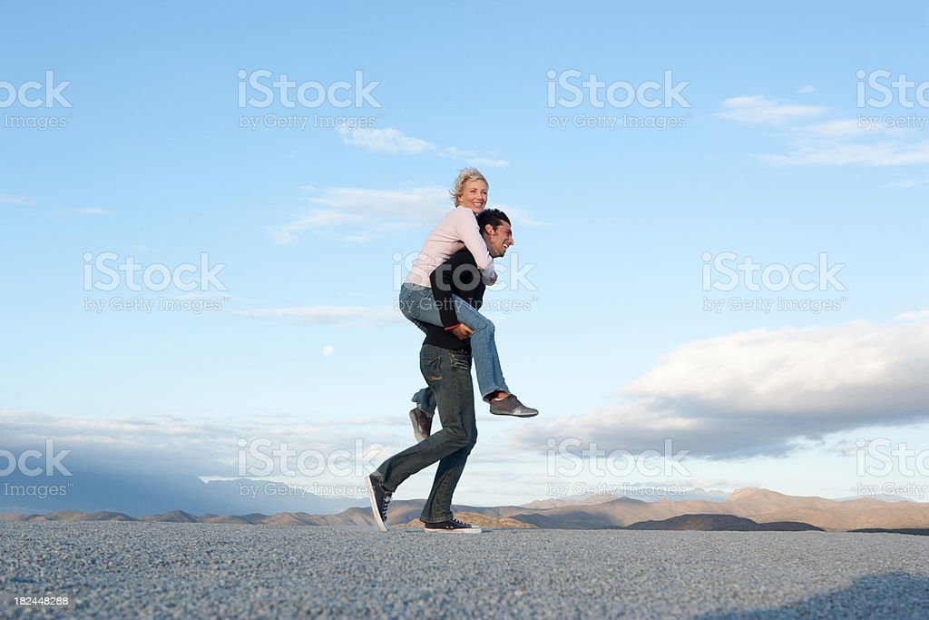 Man giving woman a piggy-back ride stock photo