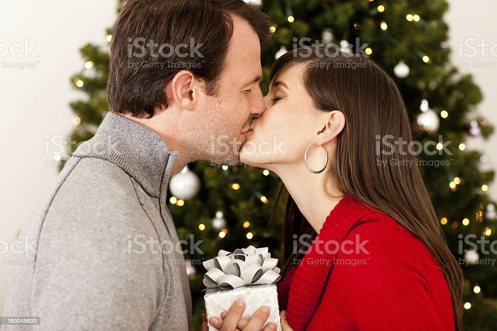 Man Giving Woman Gift And Kiss By Christmas Tree Stock Photo & More ...