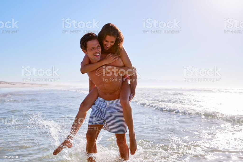 Man Giving Woman Piggyback On Summer Beach Vacation stock photo